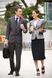 Homme d'affaires et femme d'affaires marchant le long de la rue Photo stock