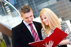 Homme d'affaires et femme d'affaires parlant au-dessus des documents Image libre de droits