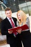 Homme d'affaires et femme d'affaires parlant au-dessus des documents Photographie stock libre de droits