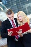 Homme d'affaires et femme d'affaires parlant au-dessus des documents Images libres de droits