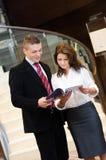 Homme d'affaires et femme d'affaires parlant au-dessus des documents Photos stock
