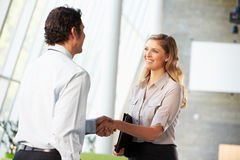 Homme d'affaires et femme d'affaires se serrant la main dans le bureau Photographie stock
