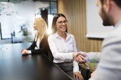 Homme d'affaires et femme d'affaires se serrant la main lors de la réunion Photographie stock libre de droits