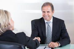 Homme d'affaires et femme d'affaires serrant la main Photographie stock