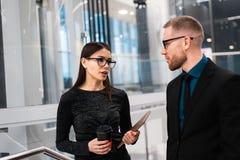 Homme d'affaires et femme d'affaires discutant quelque chose pendant la pause-café photographie stock libre de droits