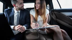 Homme d'affaires et femme d'affaires parlant sur un mouvement Image stock