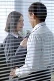 Homme d'affaires et femme se tenant dans le bureau, regardant l'un l'autre Image libre de droits
