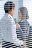 Homme d'affaires et femme se tenant dans le bureau, regardant l'un l'autre Image stock