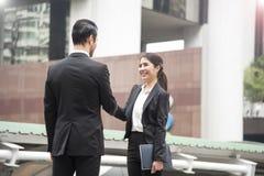 Homme d'affaires et femmes d'affaires concluant l'accord de poignée de main Images stock