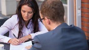Homme d'affaires et femmes d'affaires ayant une réunion en café. Elle signe un contrtact. Images libres de droits