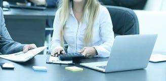 Homme d'affaires et rire auxiliaire tout en se reposant sur le lieu de travail dans le bureau Photographie stock