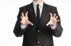 Homme d'affaires et sujet de geste : un homme dans un costume noir avec un lien montrant le geste de mains sur un fond blanc d'is Photo libre de droits
