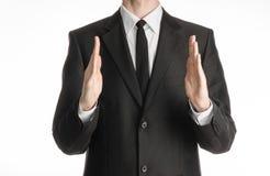 Homme d'affaires et sujet de geste : un homme dans un costume noir avec un lien montrant le geste de mains sur un fond blanc d'is Images stock