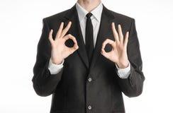 Homme d'affaires et sujet de geste : un homme dans un costume noir avec un lien montrant le signe de deux mains de l'ok d'isoleme Photographie stock
