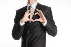Homme d'affaires et sujet de geste : un homme dans un costume noir avec un lien montrant un signe du coeur et des mains de l'amou Photographie stock libre de droits