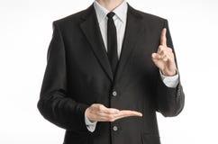 Homme d'affaires et sujet de geste : un homme dans un costume noir avec un lien montre l'index de main gauche et garde sa main dr Photos stock