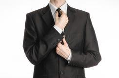 Homme d'affaires et sujet de geste : un homme dans un costume noir avec un lien redresse son lien d'isolement sur le fond blanc d Image stock