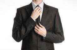 Homme d'affaires et sujet de geste : un homme dans un costume noir avec un lien redresse son lien d'isolement sur le fond blanc d Image libre de droits