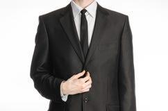 Homme d'affaires et sujet de geste : un homme dans un costume noir avec un lien redresse son lien d'isolement sur le fond blanc d Photo libre de droits