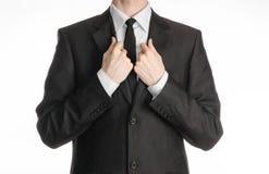 Homme d'affaires et sujet de geste : un homme dans un costume noir avec un lien redresse son lien d'isolement sur le fond blanc d Photo stock