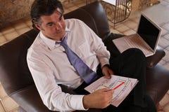 Homme d'affaires expliquant avec l'ordinateur portatif et le papier Photos stock