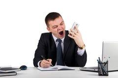 Homme d'affaires fâché avec des cris de smartphone d'isolement sur le fond blanc Images libres de droits