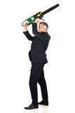 Homme d'affaires fâché avec la tronçonneuse Image stock