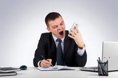 Homme d'affaires fâché avec le smartphone criant sur le fond gris Photos libres de droits