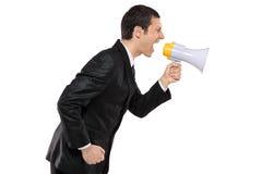 Homme d'affaires fâché criant par l'intermédiaire du mégaphone Image stock