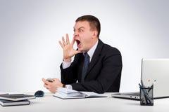 Homme d'affaires fâché criant sur le fond gris Photographie stock libre de droits
