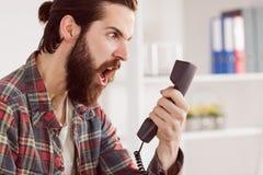Homme d'affaires fâché de hippie faisant un appel photo libre de droits