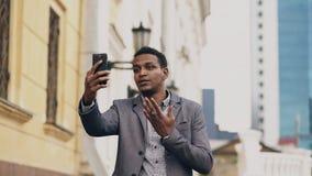 Homme d'affaires fâché de métis ayant la causerie visuelle en ligne dans la conférence d'affaires utilisant le smartphone images libres de droits