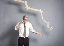 Homme d'affaires fâché devant le graphique se dirigeant vers le bas. Image libre de droits