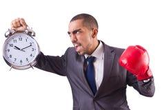Homme d'affaires fâché frappant l'horloge d'isolement Image stock