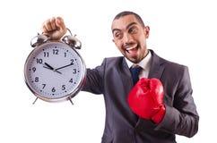 Homme d'affaires fâché frappant l'horloge d'isolement Photographie stock