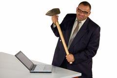 Homme d'affaires fâché heurtant l'ordinateur portatif avec le marteau de forgeron Photographie stock