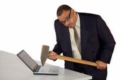 Homme d'affaires fâché heurtant l'ordinateur portatif avec le marteau de forgeron Photos libres de droits