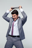 Homme d'affaires fâché heurtant son ordinateur portatif Photographie stock