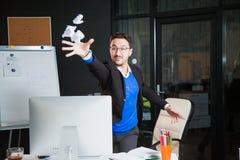 Homme d'affaires fâché nerveux d'employé de bureau de papier bouleversé de jet au bureau Photos stock