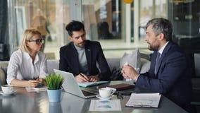 Homme d'affaires fâché parlant aux associés en café regardant des diagrammes jetant des papiers banque de vidéos