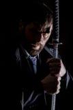 Homme d'affaires fâché sévère dans un manteau de laine avec l'épée à l'arrière-plan foncé image stock