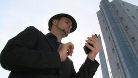 Homme d'affaires faisant des gestes sur le smartphone d'écran tactile devant l'immeuble de bureaux clips vidéos