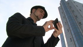 Homme d'affaires faisant des gestes sur le smartphone d'écran tactile devant l'immeuble de bureaux banque de vidéos
