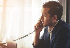 Homme d'affaires faisant l'appel dedans sur la ligne terrestre de téléphone de fax photographie stock