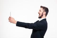 Homme d'affaires faisant le faire appel visuel au calcul de comprimé Photographie stock libre de droits
