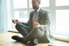 Homme d'affaires faisant le yoga photos stock