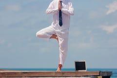 Homme d'affaires faisant le yoga sur un pont en bois avec un ordinateur portable Photos stock
