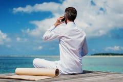 Homme d'affaires faisant le yoga sur un pont en bois avec un ordinateur portable Photos libres de droits