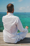 Homme d'affaires faisant le yoga sur un pont en bois avec un ordinateur portable Image stock