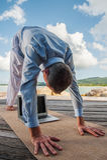 Homme d'affaires faisant le yoga sur un pont en bois avec un ordinateur portable Photo libre de droits